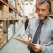 Warehouse manager writing on clipboard — Stock Photo #65565677