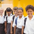 Cute schoolchildren smiling at camera by the school bus — Stock Photo #65566239