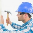 Hammering nail on wooden plank — Stock Photo #65566523