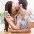 Man using smartphone while girlfriend kisses him — Stock Photo #65567275