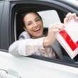 Smiling female driver tearing up her L sign — Stock Photo #65567329