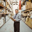 Smiling warehouse manager writing on clipboard — Stock Photo #65567539
