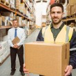 Warehouse worker smiling at camera carrying a box — Stock Photo #65567669