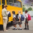 Cute schoolchildren waiting to get on school bus — Stock Photo #65568541