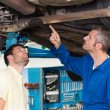 Mechanic showing customer the problem with car — Stock Photo #65568887