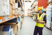 Focused warehouse worker with clipboard — Stock Photo