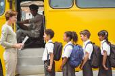 Cute schoolchildren waiting to get on school bus — Stock Photo