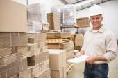 Smiling warehouse worker with clipboard — Stock Photo
