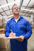 Warehouse worker checking his list — Stock Photo