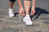 Woman tying her shoelace on running shoe — Stock Photo
