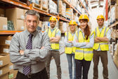 Smiling warehouse team with arms crossed — Stockfoto