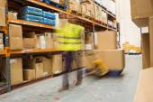 Worker pulling trolley with boxes in a blur — Stock Photo