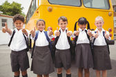 Cute schoolchildren smiling at camera by the school bus — Fotografia Stock