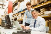 Warehouse management talking and looking at laptop — Stock Photo