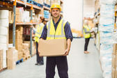 Warehouse worker smiling at camera carrying a box — Stock Photo