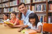 Cute pupils and teacher reading in library — Stock Photo