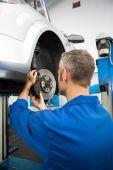 Focused mechanic adjusting the wheel — Stock Photo