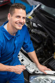 Smiling mechanic looking up at camera — Stock Photo