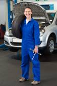 Mechanic smiling at holding tire — Stock Photo