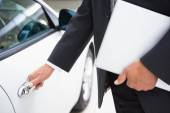 Man holding a car door handles while holding clipboard — Stock Photo