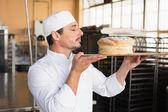 Baker smelling a freshly baked loaf — Stock Photo