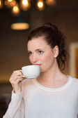 Brunette sipping cup of coffee — Stock Photo