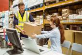 Warehouse worker and manager passing a box — Stock Photo