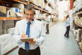 Smiling warehouse manager writing on clipboard — Stock Photo