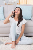 Pretty brunette laughing on the phone — Stockfoto