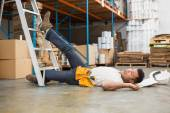 Worker lying on floor in warehouse — Stock Photo