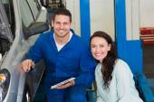Mechanic and customer smiling at camera — Stock Photo