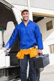 Handsome handyman holding toolbox — Stock Photo