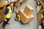 Worker with trolley of boxes smiling at camera — Stockfoto