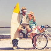 Cute couple with bike and surfboard — Stock Photo