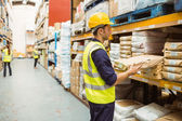 Warehouse worker taking package in the shelf — Stock Photo