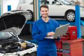 Smiling mechanic using his laptop — Stock Photo
