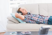 Man napping on sofa with music — Stock Photo