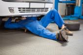 Mechanic lying and working under car — Stockfoto