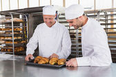 Bakers looking trays of croissants — Stock Photo