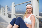 Fit blonde sitting on the pier — Stock fotografie