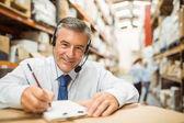 Jefe de almacén sonriente escribiendo en portapapeles — Foto de Stock
