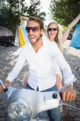 Attractive couple riding a scooter — Stock Photo