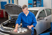 Focused mechanic inflating the tire — Stock Photo