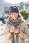 Blonde in warm clothes text messaging — Stock Photo