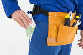 Repairman putting euro notes in pocket — Stock Photo