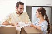 Couple unpacking boxes in kitchen — Stock Photo