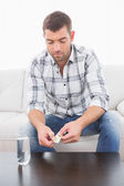 Hungover man with his medicine laid out on coffee table — Stock Photo