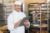 Smiling baker writing on clipboard — Stock Photo
