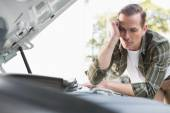 Upset man checking his car engine after breaking down — Stock Photo