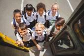 Cute schoolchildren getting on school bus — Stock Photo